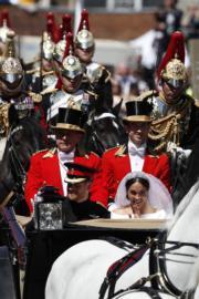 2018年5月19日,英國哈里王子(左)與梅根(右)坐馬車巡遊。(法新社)