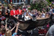 2018年5月19日,英國哈里王子與梅根結婚,二人乘坐馬車向民眾揮手。(新華社)