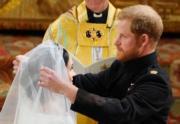 英國哈里王子(右)與梅根(左)5月19日舉行婚禮,新郎為新娘揭起頭紗。(法新社)