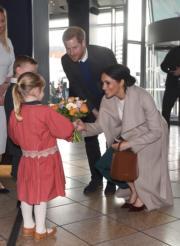 馬克爾(右一)與哈里王子(右二)獲小朋友送花。(法新社)
