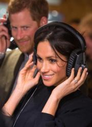 馬克爾(前)戴着耳機時,哈里王子(後)情深款款看着她。(法新社)