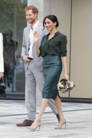 2018年10月3日,梅根(右)穿上& Other Stories深綠色絲綢上衣,Hugo Boss綠色鉛筆裙及Stuart Weitzman米色高跟鞋,與哈里王子(左)一起訪問薩塞克斯。(法新社)