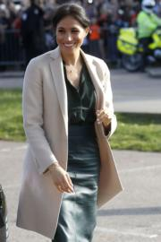 梅根在綠色色調的衣著造型外配上Giorgio Armani米黃色外套。(法新社)
