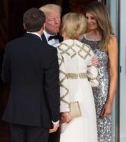 法國第一夫人布麗吉特 (前排右)穿上白色長裙,手袖及腰上綴飾金銀邊細節。(法新社)
