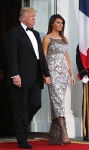 美國第一夫人梅拉尼婭(右)以銀色高跟鞋配銀色長裙。左為美國總統特朗普。(法新社)