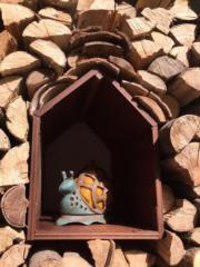 小花園內,一塊塊木頭砌成「蝸牛」的小房子。(黃廷希攝,圖片攝於2017年4月)