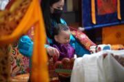 2021年4月14日,不丹二王子Jigme Ugyen Wangchuck坐在王后佩馬懷中,露出可愛笑容。(Jetsun Pema facebook圖片)