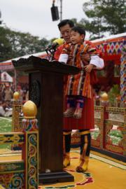 2018年12月17日,不丹舉行國慶活動,國王基沙爾(後)在講台上抱起小王儲(前)。(His Majesty King Jigme Khesar Namgyel Wangchuck facebook圖片)