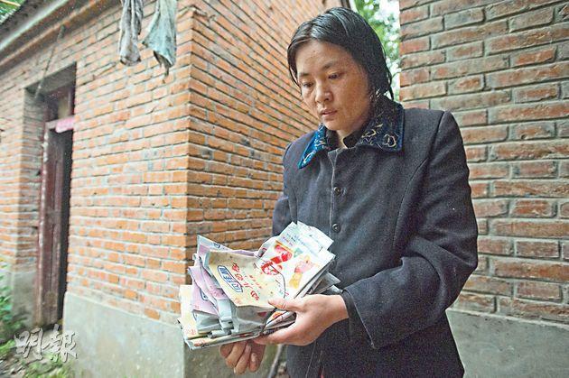 宋悅悅母親王秀麗拿着假奶粉的袋子,回憶舊事十分自責。(鄧宗弘攝)