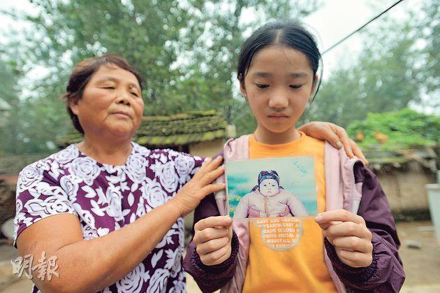 苗雨婷(右)拿着自己患病時的照片,左為祖母張俠。(鄧宗弘攝)