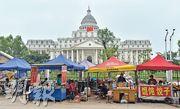 阜陽市潁泉區政府被當地人戲稱「白宮」,與旁邊的小吃街對比鮮明。(鄧宗弘攝)