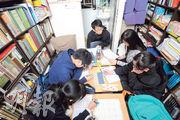 補習老師林小龍(中)說,學生多的時候,因劏房內空間不足,他要坐到廁所裏面教書,之前要坐馬桶或蹲,他現時將水桶倒冚在地上當櫈子坐。(胡景禧攝)