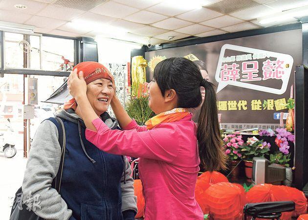 薛媽媽(左)既是女兒競選的出資人,也是助選團,圖為薛呈懿(右)為媽媽戴上競選頭巾。(陳淑安攝)