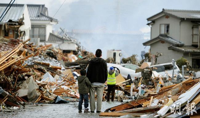 2011年3月11日,日本發生有紀錄以來最強烈的9級地震,促成後來的建築條例修訂。圖為仙台市居民當年看着被海嘯冲毁的家園。(資料圖片)