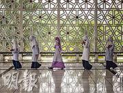 馬來西亞有超過六成的穆斯林人口,在吉隆坡的國家清真寺中,參與禱告後的婦女走過空曠的大廳。(李澤彤攝)