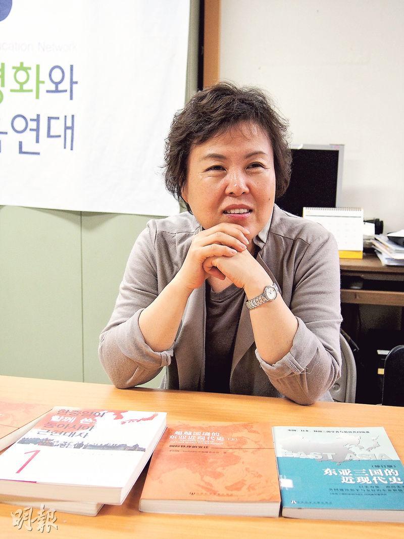 韓國民間教科書關注組織「亞洲和平及歷史教育連帶」常任共同運營委員長梁美康向記者介紹桌上由中日韓3國學者編著的歷史教科書,坦言14年來工作漫長艱辛,但自己從中得益不少。(林康琪攝)