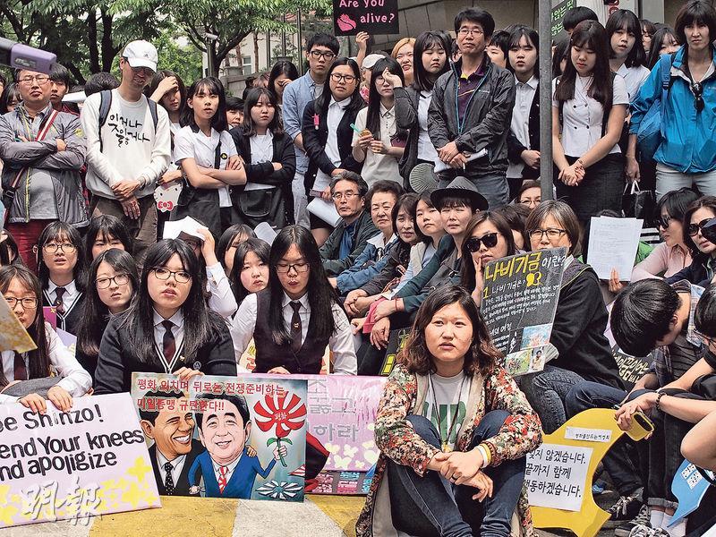 在日本大使館門外的集會上,韓國示威者展示繪有美國總統奧巴馬及日本首相安倍晉三的漫畫,諷刺美國縱容日本。(林康琪攝)