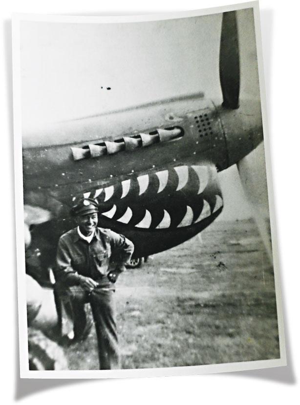 廖譚清在以鯊魚牙塗裝在機首的飛虎隊P-40戰鬥機前留影。(受訪者提供)