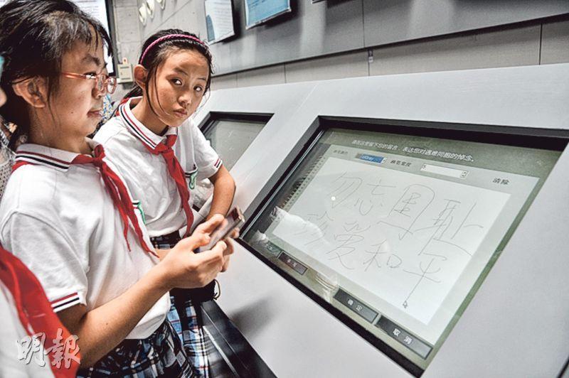 兩名南京小學生在大屠殺紀念館的電子留言板上寫下﹕勿忘國恥,珍愛和平。(楊立贇攝)