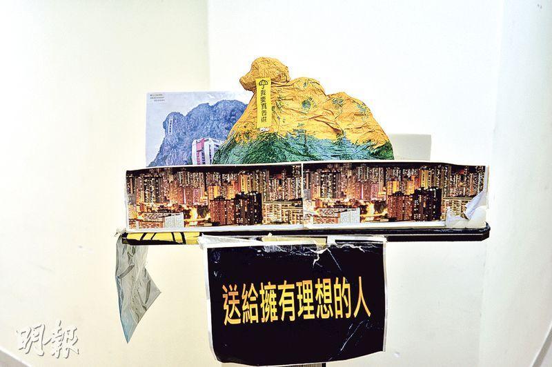 第一獅山——有市民登上獅子山掛起「我要真普選」巨型直幡後,佔領區出現不少獅子山模型,這個以紙、皺紋膠紙製作、最土炮的「獅子山」乃是第一個,當時擺放於金鐘連儂牆附近。(蘇智鑫攝)
