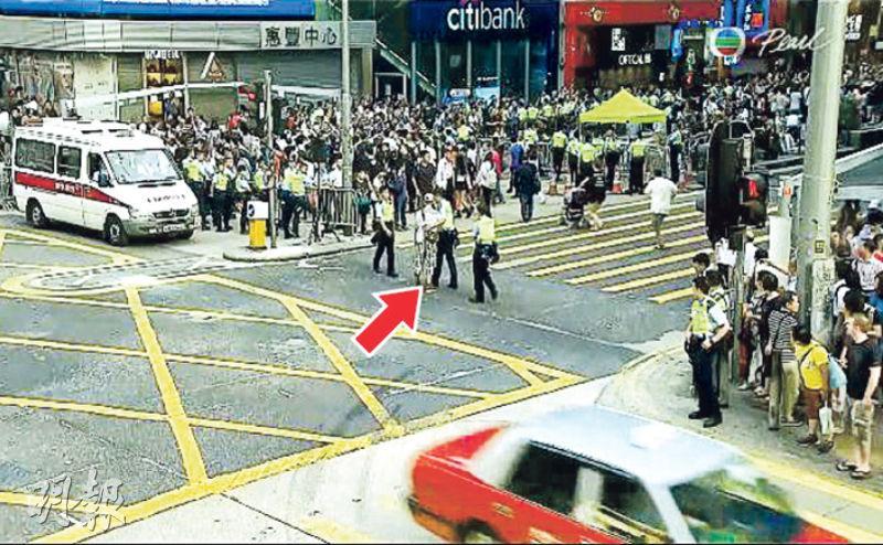 控方曾指被告郭偉衡(箭嘴示)坐在彌敦道堵塞馬路,攔着一輛平治私家車,惟從現場的新聞片段上並不能看到控方所指稱的情况。(資料圖片)