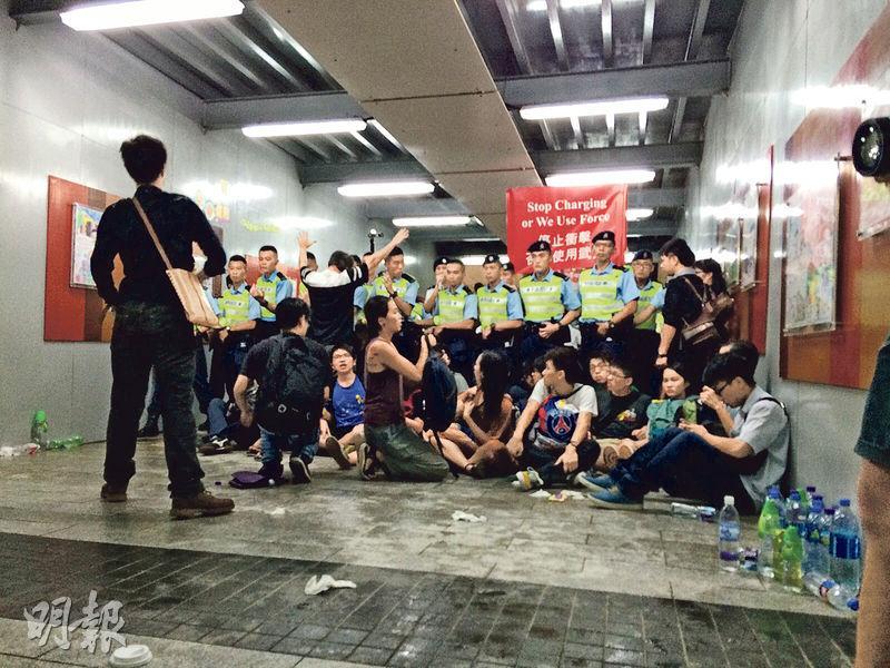 當日有示威者困在「公民廣場」與立法會大樓之間的通道,為免再起衝突,示威者手挽手坐於警察腳旁,警察當時高舉紅旗警告,氣氛持續緊張。(受訪者提供)