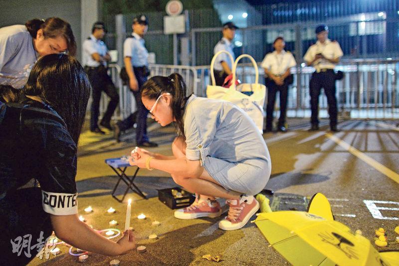 昨日黃昏後,金鐘添美道政府總部外開始有市民聚集,警方亦較昨日中午時派出更多人手巡邏。圖為有市民於政總門外點起燭光紀念。(鄧宗弘攝)