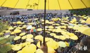 昨日不少市民重返金鐘,出席民陣與民間團體舉行的佔領運動一周年集會;其間市民響應大會呼籲,於傍晚5時58分、即一年前警方發射第一枚催淚彈驅散市民的時間,舉起黃傘默站15分鐘。同一時間,身穿藍色制服的警員,在圖中遠處築起重重人牆及鐵馬陣,防止有人衝出夏愨道。警方稱,昨有1100人在政總一帶參與活動,當中包括180名反佔中者。(鍾林枝攝)