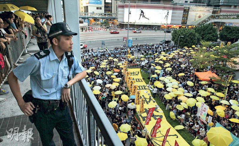 民陣聯同民間團體昨在政府總部對開行人路舉行「全民反政治打壓運動」集會,紀念佔領運動一周年。大會在傍晚5時58分、即去年警方發射第一枚催淚彈驅散市民的時間,帶領市民舉起黃傘默站15分鐘。警員則在中信天橋上監視集會情况。(林俊源攝)