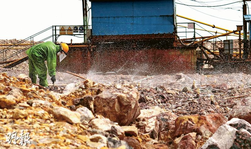 露天堆場裏,工人會向礦石噴灑氰化鈉溶液,將黃金溶出來,再收集金水運往冶煉廠提取黃金。(明報記者攝)