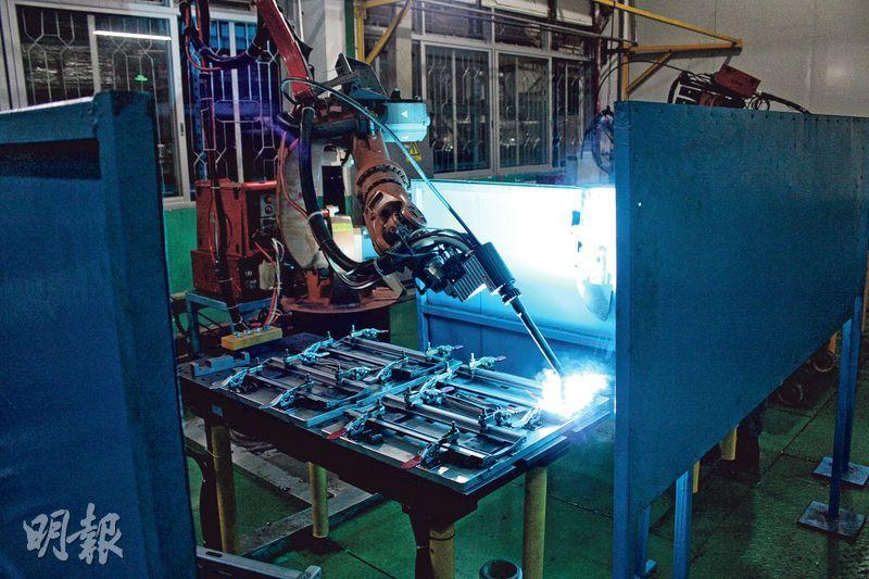佛山海信科龍的燒焊車間裏,正在焊接電視機金屬支架的機械人噴出藍色火焰。(楊立贇攝)