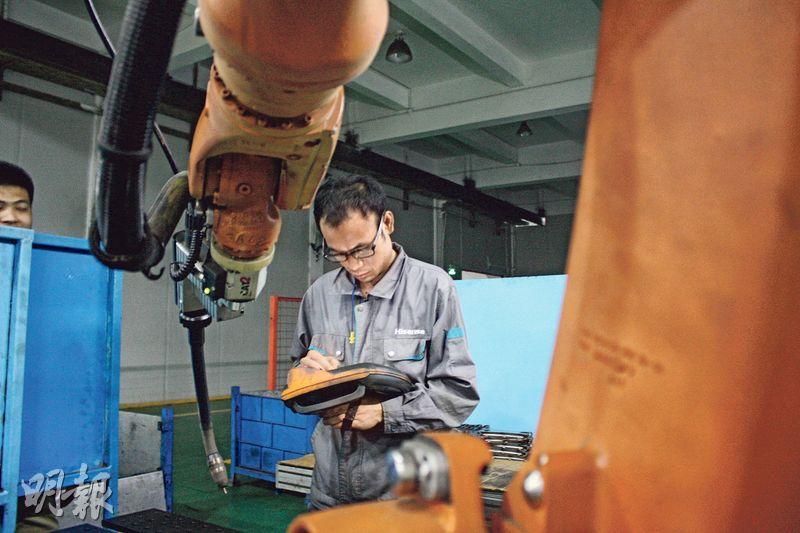 佛山海信科龍燒焊車間班長楊國成在檢查機械人故障。(楊立贇攝)