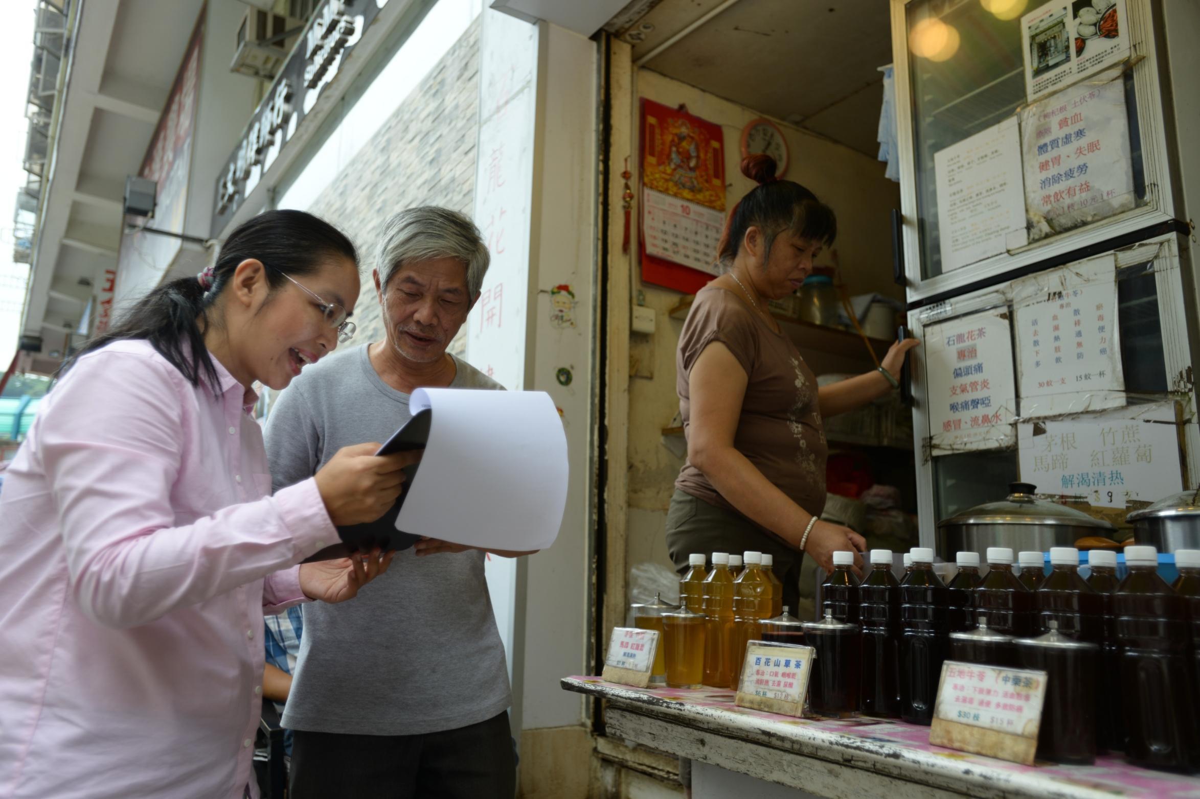 第一次參選的蔡咏梅(左)找小店貼海報,要店主同意及簽授權書,這些手續上的要求,她邊做邊學。(黃志東攝)