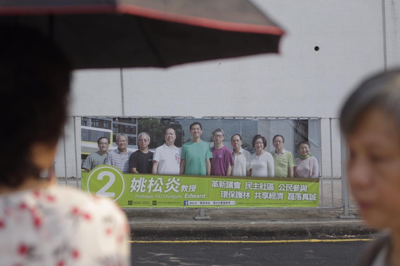 姚松炎強調是次以整個團隊參選,有別其他候選人,姚松炎不願在宣傳橫額只擺放自己的「大頭照」,而選用10人團隊的照片。(郭慶輝攝)