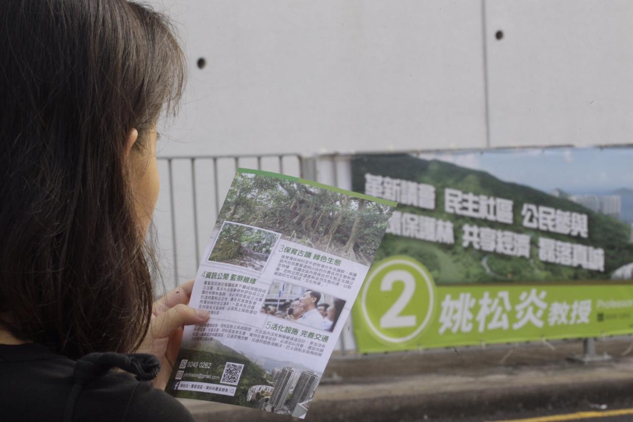 姚松炎的宣傳橫額上印有是用區內的置富山谷,表達自己關注保育、環保議題。(郭慶輝攝)