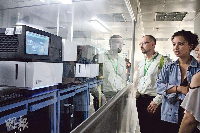 上月參加第10屆國際基因組學大會的業內專家和媒體人士在深圳華大參觀基因測序實驗室。(楊立贇攝)