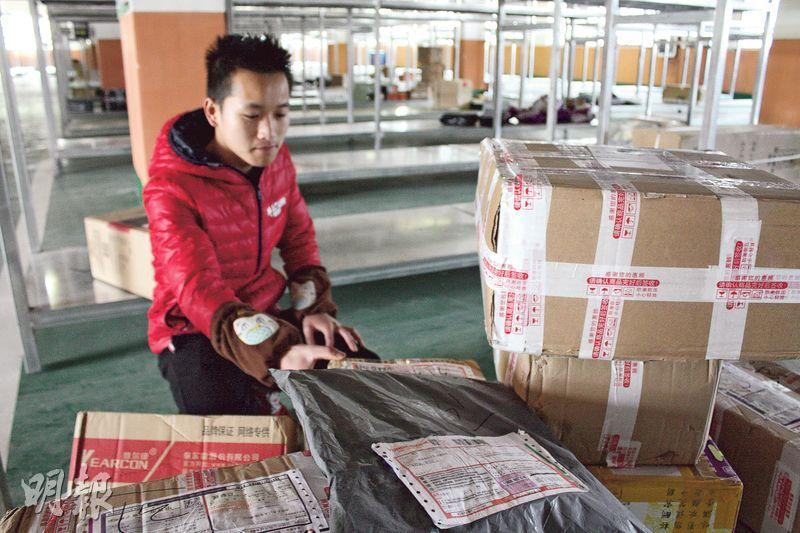 貴州威寧縣的農村淘寶貨倉管理員韋義在整理快遞包裹。(楊立贇攝)