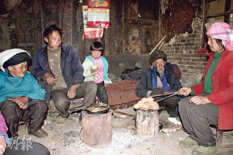 貴州威寧縣貧困戶王友柱(左二)與母親(左一)、父親(右二)、小女兒(中)圍坐在火爐旁,其妻鄧彩彩(右一)則在烤薯仔。(楊立贇攝)