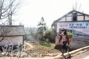 貴州一名農村少女揹着蔬菜在路上走着。電子商貿在中國西部仍在起步,目標是將農產品送到全國。(楊立贇攝)