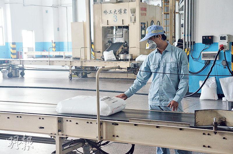 生產車間內,流水線輸送着一包包產品,工人全部戴有防護口罩。(明報記者攝)
