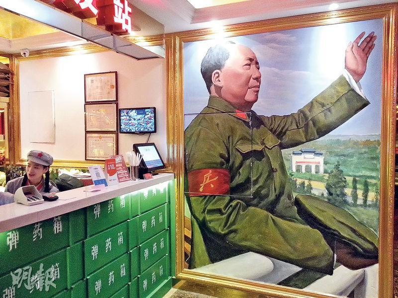 重慶「老基地」火鍋店標明「紅色文化主題」,店內充滿文革元素。收銀台的背景是文革期間毛澤東接見紅衛兵的畫像。(明報記者攝)