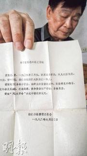 黄家樑(化名)向記者展示他父親和兄弟的死亡證明。文革中他父親和兄弟避禍鄉間,反被捉住殺害,內臟也被挖了出來。(明報記者攝)