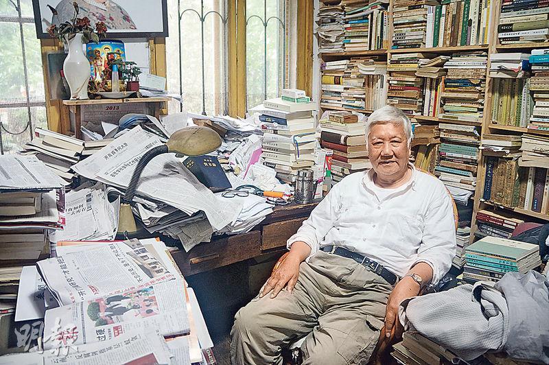 文革時為上海市委寫作組負責人的朱永嘉,他的書房堆滿書報,他正對照枱面上的上海《文匯報》刊登的習近平講話,翻閱馬克思的《資本論》(深藍色封面)。(林迎攝)