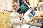 李正天說當年被「發配」到粵北礦山勞動的經歷,對他後來的創作有很大影響。圖為他在工作室裏展示自己的畫冊。(劉利攝)