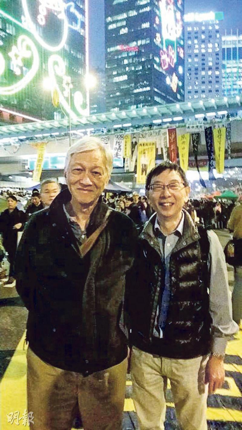 經歷六七暴動的黃耀堃(右),在2014年佔領運動期間不時到金鐘探望學生和朋友,佔領接近尾聲時,他在金鐘遇到1970年代在出版界認識的時事評論員李怡(左),並與他合照。(黃耀堃提供)