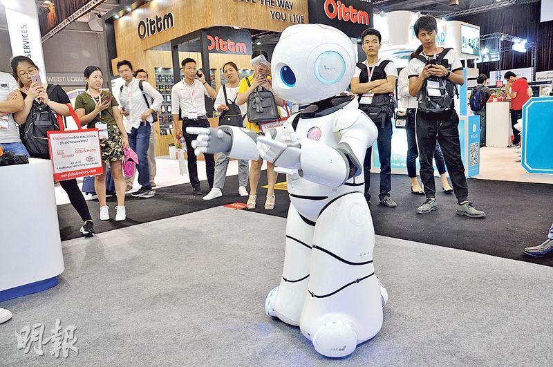 在香港亞洲國際博覽館舉行的環球資源電子展上,由深圳量旌科技公司生產、懂得跳舞和可以與客戶對答的機械人吸引了不少人圍觀。(明報記者攝)