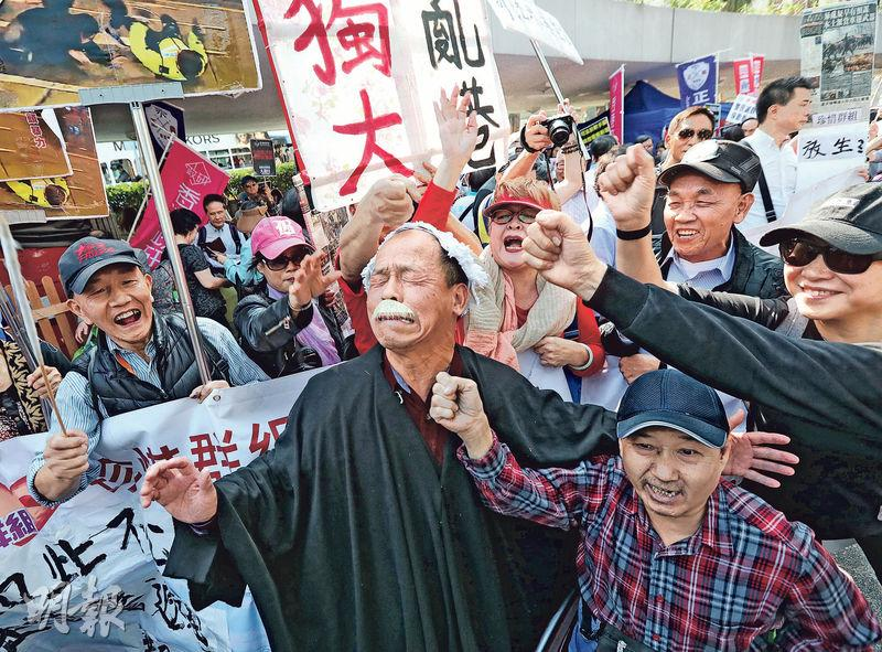 七警案中7名警員因襲擊曾健超罪成,服務香港司法機構逾20年的英籍法官杜大衛判處7人監禁兩年。事後有團體發起撐警遊行,有人頭戴假髮及身穿黑袍扮成法官,旁人作狀出拳打他(圖)大喊「打倒狗官」。(資料圖片)