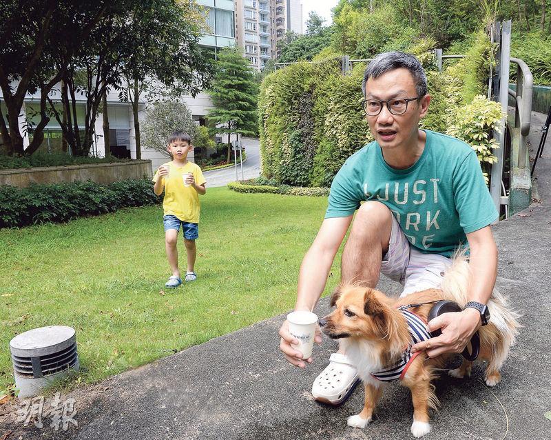 在港無法一展所長,再次北上工作的Danny(右),雖對本港困局感沮喪,但仍積極享受生活,珍惜假日回港「放放狗,跑跑公園」的天倫之樂,笑稱其手抱小狗是在北京收養,現隨家人回流香港成了「新移民」。(劉焌陶攝)