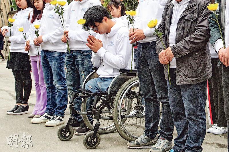 鄭海洋(坐輪椅者)10年前在地震中失去雙腿,今年清明節與北川中學其他倖存師生一起,返回舊校址拜祭同學。(曾憲宗攝)