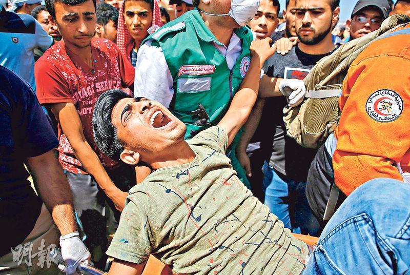 昨日在加沙邊境的巴人示威者遭以軍用實彈攻擊,救援人員和其他巴人合力抬起一名受傷巴人男子。